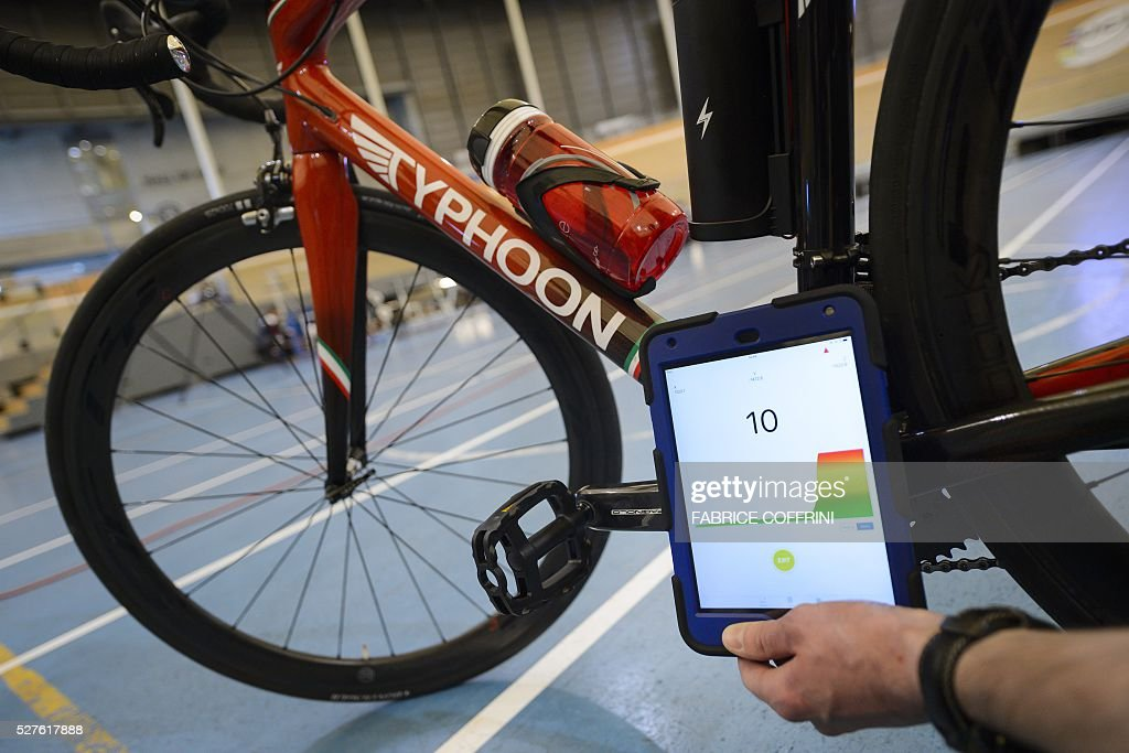 A staff member of the International Cycling Union (UCI) holds a tablet to scan a bicycle during a demonstation on testing technological fraud at the UCI headquarters in Aigle, western Switzerland, on May 3, 2016. The tablet scans a bicycle with magnetic resistance technology, testing the frame and wheels in less than a minute in order to detect mechanical doping during cycling races. / AFP / FABRICE
