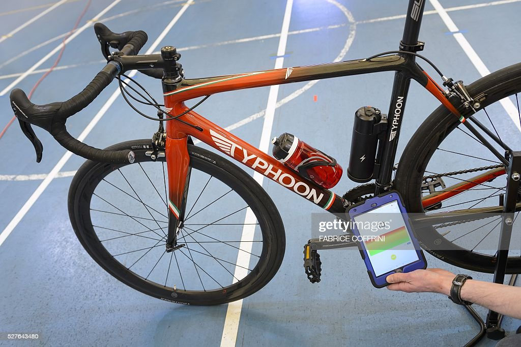 A staff member of the International Cycling Union (UCI) holds a tablet to scan a bicycle during a demonstation on testing technological fraud and detecting the presence of a motor inside the frame at the UCI headquarters in Aigle, western Switzerland, on May 3, 2016. The tablet scans a bicycle with magnetic resistance technology, testing the frame and wheels in less than a minute in order to detect mechanical doping during cycling races. / AFP / FABRICE
