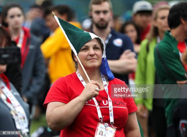 TORONTO ON JULY 22 A staff member of the Yukion team Therese Lindsay protects herself from the rain with a flag The Closing Ceremony for NAIG 2017...