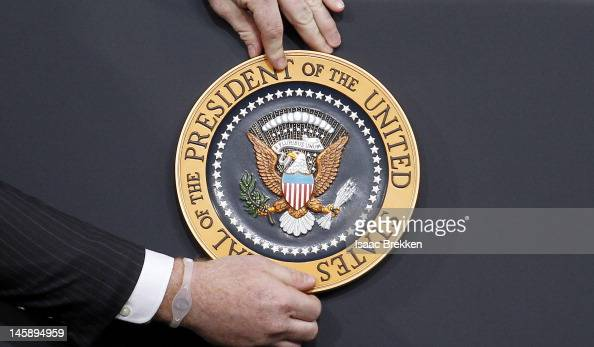 A staff member places the Seal of the President of the United States on a podium before US President Barack Obama spoke at the University of Nevada...