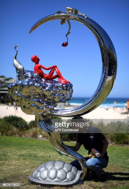 A staff member polishes a sculpture by artist Chen Wenling from China at the 'Sculpture by the Sea' exhibition near Bondi beach in Sydney on October...