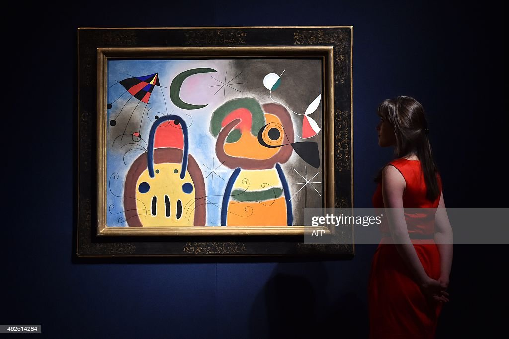 A staff member poses for pictures next to a painting by <a gi-track='captionPersonalityLinkClicked' href=/galleries/search?phrase=Joan+Miro&family=editorial&specificpeople=190767 ng-click='$event.stopPropagation()'>Joan Miro</a> entitled 'L'Oiseau au plumage deploye vole vers l'arbre argente,' which is estimatd at 7-9 million British pounds (10.5-13.5 million USD, 9-12 million Euros), during the impressionist, modern and surreal art preview at Christie's auction house in central London on January 30, 2015.