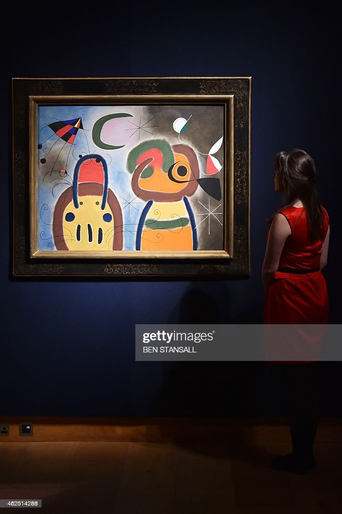 A staff member poses for pictures next to a painting by <a gi-track='captionPersonalityLinkClicked' href=/galleries/search?phrase=Joan+Miro&family=editorial&specificpeople=190767 ng-click='$event.stopPropagation()'>Joan Miro</a> entitled 'L'Oiseau au plumage deploye vole vers l'arbre argente,' which is estimatd at 7-9 million British pounds (10.5-13.5 million USD, 9-12 million Euros), during the impressionist, modern and surreal art preview at Christie's auction house in central London on January 30, 2015. AFP PHOTO / BEN STANSALL == RESTRICTED TO EDITORIAL USE, MANDATORY MENTION OF THE ARTIST, TO ILLUSTRATE THE EVENT AS SPECIFIED IN THE CAPTION ==