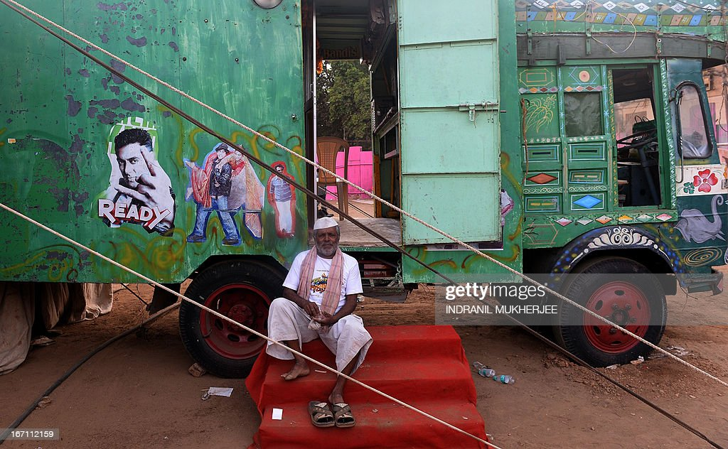 A staff member prepares chewing tobacco as he sits on the steps of the 'projection truck' at the Anup Touring Talkies tent cinema at a ground in central Mumbai on April 19, 2013. To mark 100 years of Indian Cinema, a Marathi film 'Touring Talkies' is being screened in a makeshift tent theatre just like the days of yore, in its pre-multiplex and pre-single screen glory dating back 50 years. The tents, keeping in mind modern audiences, will have plush seating, air conditioning and popcorn and cola alongside fresh sugar-cane juice, roasted groundnuts and gram and pickle and other tit-bits. The cinema will screen four shows per day for a week. The idea of touring talkies was the brainchild of the doyne of Indian cinema, Dadasaheb Phalke, after he saw the British watching movies in tents. The touring cinema would travel through rural India and screen movies in makeshifts tents. At present, one can only find these talkies - whose sweltering tents and basic facilities contrast with the plush, air-conditioned multiplexes springing up in Indian cities, during Jatras (village fairs) in the interiors of the state.