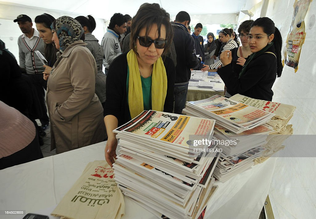 LAMBROSCHINI - A staff member prepares programs on a table ahead of the opening of the World Social Forum (WSF) on March 23, 2013 in Tunis. More than two years after the Jasmine revolution, tens of thousands of people are expected for the WSF, dubbed the forum of 'dignity', a watchword of the Tunisian uprising that inspired revolts across the Arab world. The event takes place from March 26 to 30.
