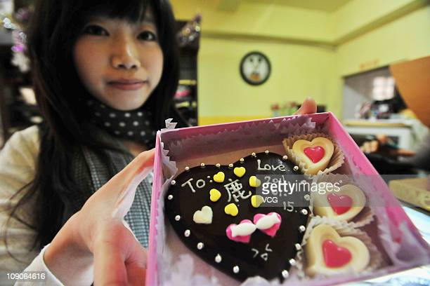 A staff member presents a 'Do It Yourself' chocolate gift box at a gift shop on February 13 2011 in Qindao Shandong province of China