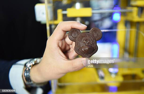 A staff member shows a 3D printed chocolate during the CES Asia 2016 on May 11 2016 in Shanghai China