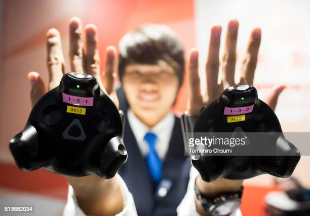 A staff member shows HTC Corp virtual reality trackers as he tries the Mario Kart Arcade GP VR attraction at the VR Zone Shinjuku theme park operated...