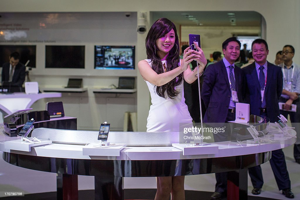 A staff member shows takes a picture of herself using a Huawei smartphone during the CommunicAsia2013, EnterpriseIT2013 and BroadcastAsia2013 Exhibition and Conference at Marina Bay Sands on June 18, 2013 in Singapore. The conference draws over 2000 companies and showcases the latest developments and trends from communication technology, broadcast, digital multimedia and entertainment technology industries.