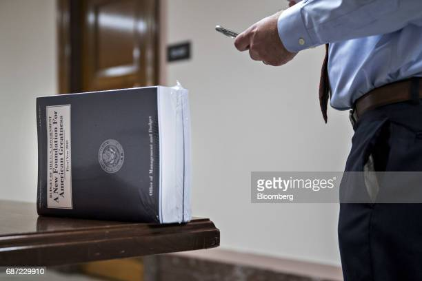 A staff member stands next a copy of US President Donald Trump's fiscal 2018 budget proposal on Capitol Hill in Washington DC US on Tuesday May 23...