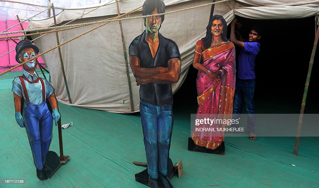 A staff member ties the entrance curtain after a show as cut-outs of Bollywood actor-director Raj Kapoor (L), Sunny Deol (C) and Kajol are seen at the Anup Touring Talkies tent cinema at a ground in central Mumbai on April 19, 2013. To mark 100 years of Indian Cinema, a Marathi film 'Touring Talkies' is being screened in a makeshift tent theatre just like the days of yore, in its pre-multiplex and pre-single screen glory dating back 50 years. The tents, keeping in mind modern audiences, will have plush seating, air conditioning and popcorn and cola alongside fresh sugar-cane juice, roasted groundnuts and gram and pickle and other tit-bits. The cinema will screen four shows per day for a week. The idea of touring talkies was the brainchild of the doyne of Indian cinema, Dadasaheb Phalke, after he saw the British watching movies in tents. The touring cinema would travel through rural India and screen movies in makeshifts tents. At present, one can only find these talkies - whose sweltering tents and basic facilities contrast with the plush, air-conditioned multiplexes springing up in Indian cities, during Jatras (village fairs) in the interiors of the state.