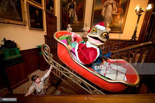 A staff member watches as a Christmas display of Mr Toad a character from the classic children's book 'The Wind in the Willows' sat in a sleigh is...