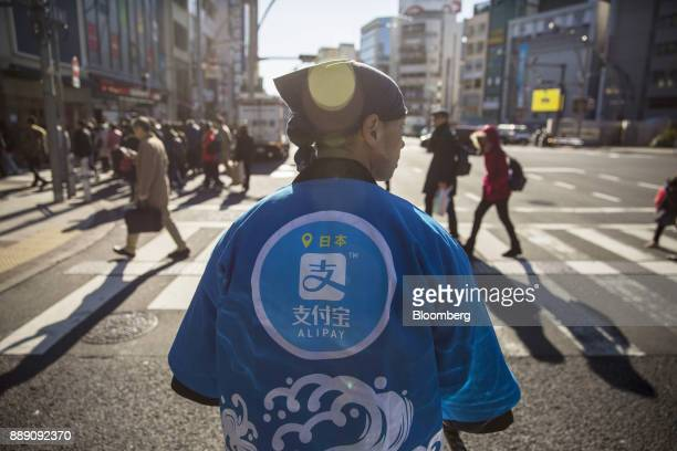 A staff member wearing a uniform featuring the logo for Ant Financial Services Group's Alipay an affiliate of Alibaba Group Holding Ltd stands during...