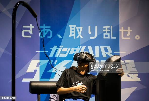 A staff member wearing a virtual reality headset tries the Gundam VR Daiba Assault VR attraction at the VR Zone Shinjuku theme park operated by...