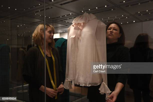 Staff members adjust a 1981 Emanuel pale pink chiffon blouse with satin neckribbon worn during Diana's first official portrait in 1981 during a...