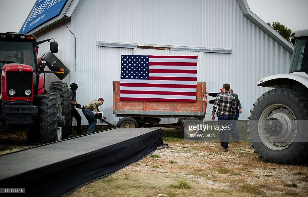 Staff members and volunteers set up the stage at the James Koch Farm in Van Meter Iowa October 9 2012 ahead of US Republican presidential candidate...