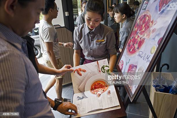 Staff members attend to customers browsing the menu and entering Pizza Hut's first restaurant in Yangon on October 22 2015 Pizza Hut is to open its...