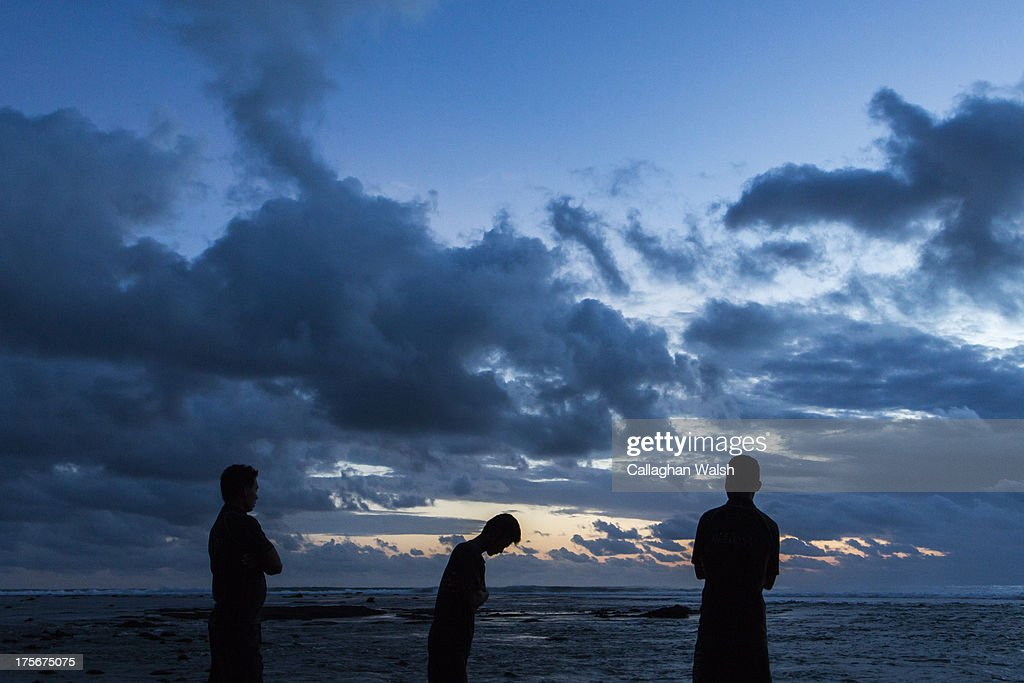 Staff members from Nihiwatu Resort look out over the water during sunset at Nihiwatu Beach, Western Sumba on April 11, 2013. Sumba is a remote island in Eastern Indonesia, part of the Lesser Sunda Islands group based in the province of East Nusa Tenggara.