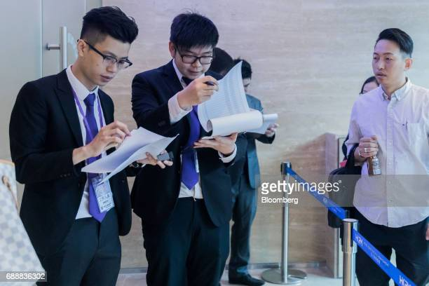 Staff members look at paper work outside the sales office of the Victoria Skye residential development developed by KK Property Holdings Ltd in Hong...