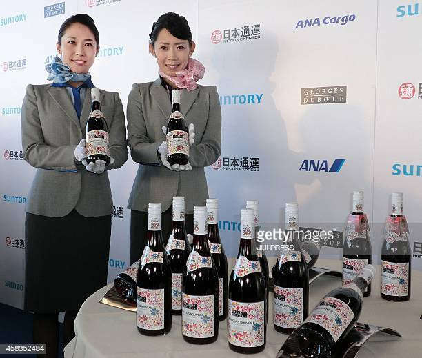 Staff members of All Nippon Airways display bottles of 2014 Beaujolais Nouveau wine made in Bourgogne just after the arrival at Haneda Airport in...