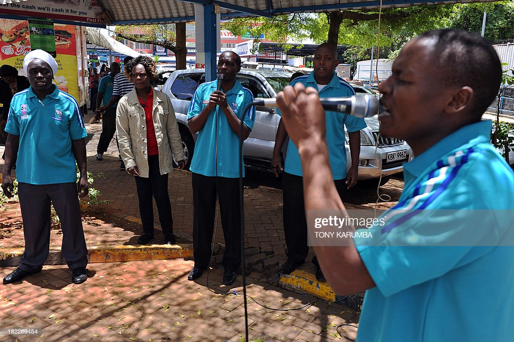 Staff members of Nakumatt supermarkets, who survived the four-day siege by Somali jihadists earlier in the week, pray on September 29, 2013 for the victims outside the Westgate mall. Pressure mounted on the Kenyan authorities a week after the Nairobi mall carnage amid questions over the fate of the missing and accusations on September 28, 2013 that top brass failed to heed security warnings. President Uhuru Kenyatta has vowed not to bow to the Shebab group that claimed the Westgate mall bloodbath and threatened more attacks if Kenya failed to pull its troops out of Somalia. AFP PHOTO/Tony KARUMBA