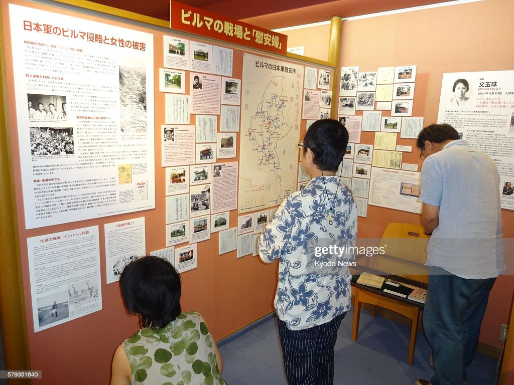 Staff members of the Women's Active Museum on War and Peace in Tokyo check panels on display on July 13 during an exhibition about sexual violence...