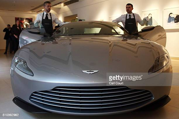 Staff members pose with one of the Aston Martin DB10's used in the Bond film Spectre during a photocall at Christie's auction house on February 15...