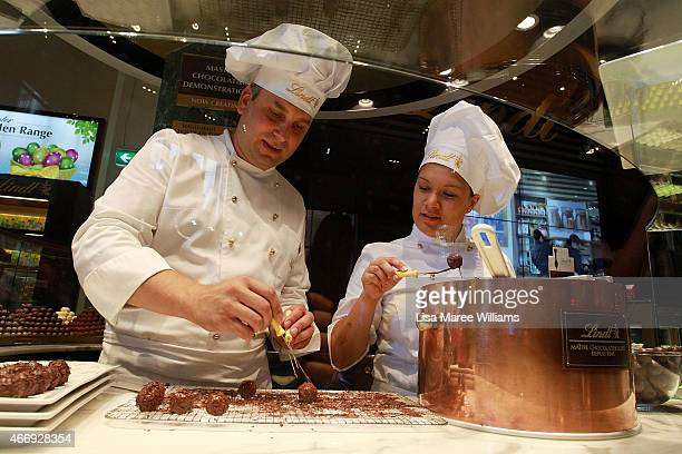 Staff members prepare chocolate at the Lindt Cafe in Martin Place on March 20 2015 in Sydney Australia The cafe reopened to the public today three...