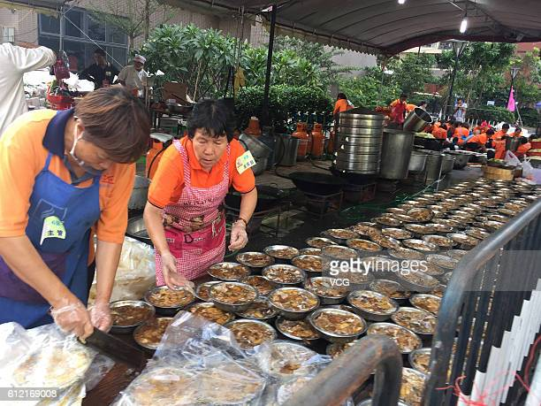 Staff members prepare the housewarming feast for over 10000 moveback villagers in Yangji Village on October 2 2016 in Guangzhou China Over 10000...