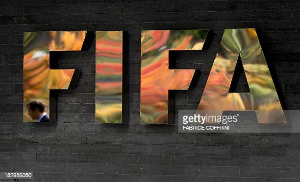 A staff member's reflection of global football's governing body FIFA is seen in its logo on October 3 2013 at its headquarters in Zurich FIFA kicked...