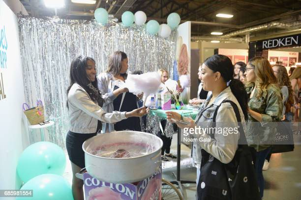 Staff members serve guests cotton candy during Beautycon Festival NYC 2017 at Brooklyn Cruise Terminal on May 20 2017 in New York City