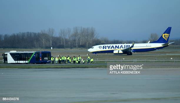 Staff members stand on the tarmac next to an aircraft of Irish lowcost Ryanair airline on December 1 2017 at the Liszt Ferenc international Airport...
