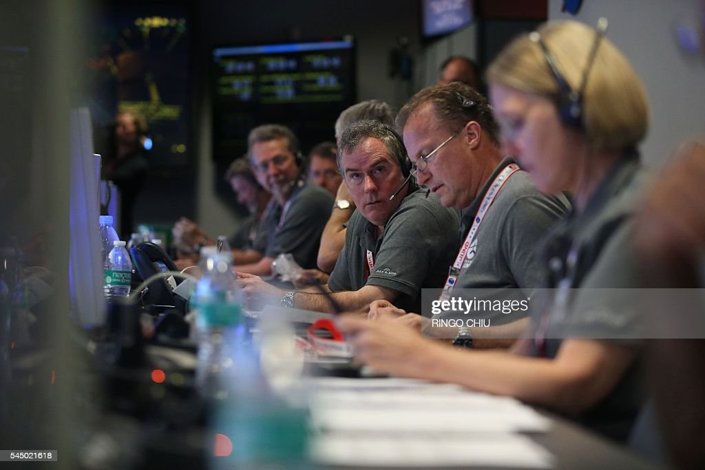 Staff members watch on before the solar-powered Juno spacecraft went into orbit around Jupiter, at NASA's Jet Propulsion Laboratory in Pasadena, California on July 4, 2016. Juno was launched from Cape Canaveral in Florida on August 5, 2011 on a five-year voyage to its mission to study the planet's formation, evolution and structure. / AFP / POOL / Ringo Chiu