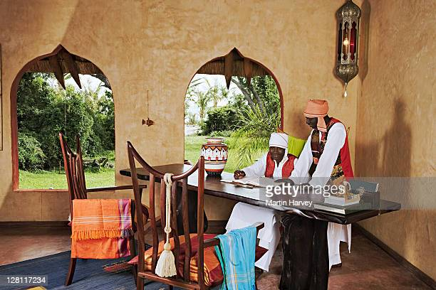 Staff members welcome guests at the reception desk of the luxurious Benguerra Lodge. Mozambique. (MR) (PR: Property released)