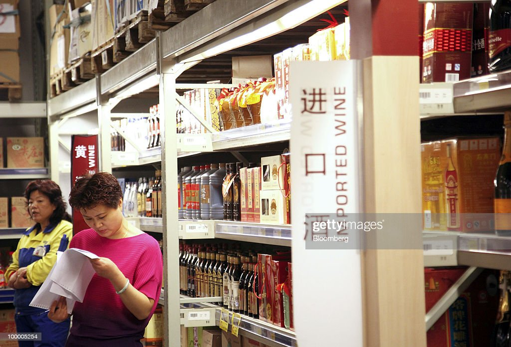 Staff members work in the imported wine department at a Metro AG supermarket in Shanghai, China, on Wednesday, May 19, 2010. Metro AG, Germany's largest retailer, plans to add 100 stores worldwide this year, the company said in a statement issued in Shanghai today. Photographer: Qilai Shen/Bloomberg via Getty Images