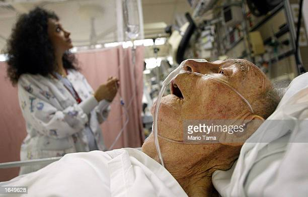 Staff nurse Judith Marini checks an elderly man's IV in the emergency room at Coney Island Hospital October 4 2002 in the Brooklyn borough of New...