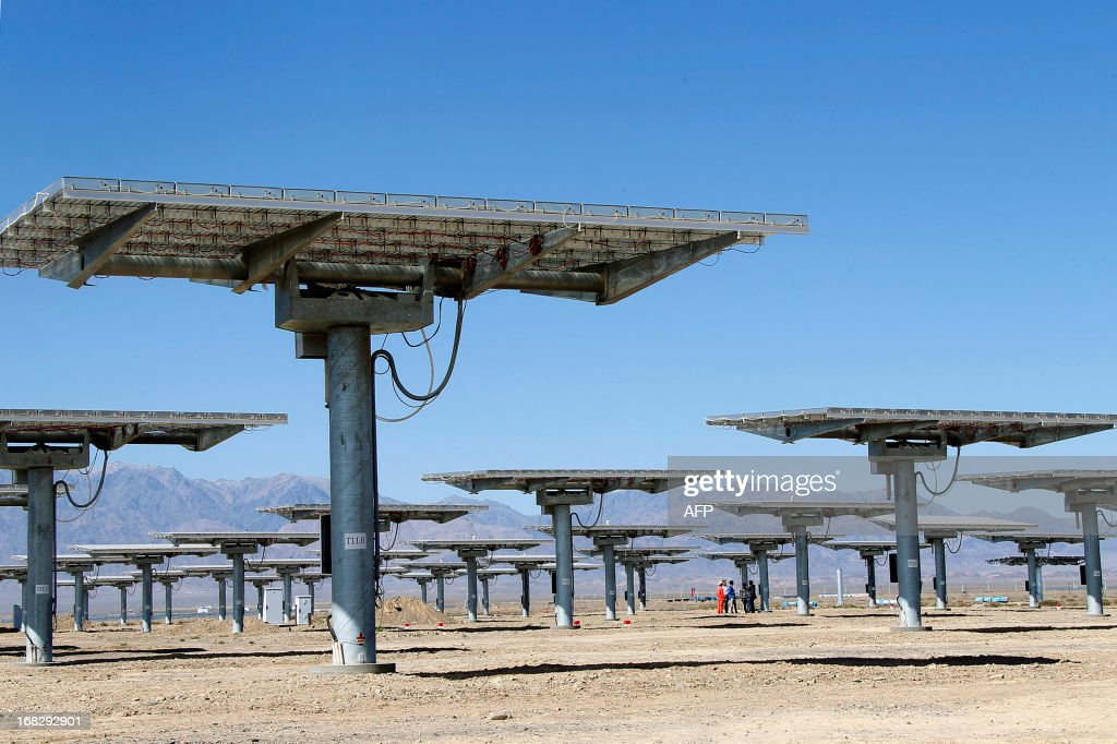 Staff of a solar power plant works on their solar panels in Hami, northwest China's Xinjiang Uygur Autonomous Region on May 8, 2013. The EU executive on May 8 proposed heavy anti-dumping tariffs of around 47 percent on imports of Chinese solar panels, a European Union source said. CHINA