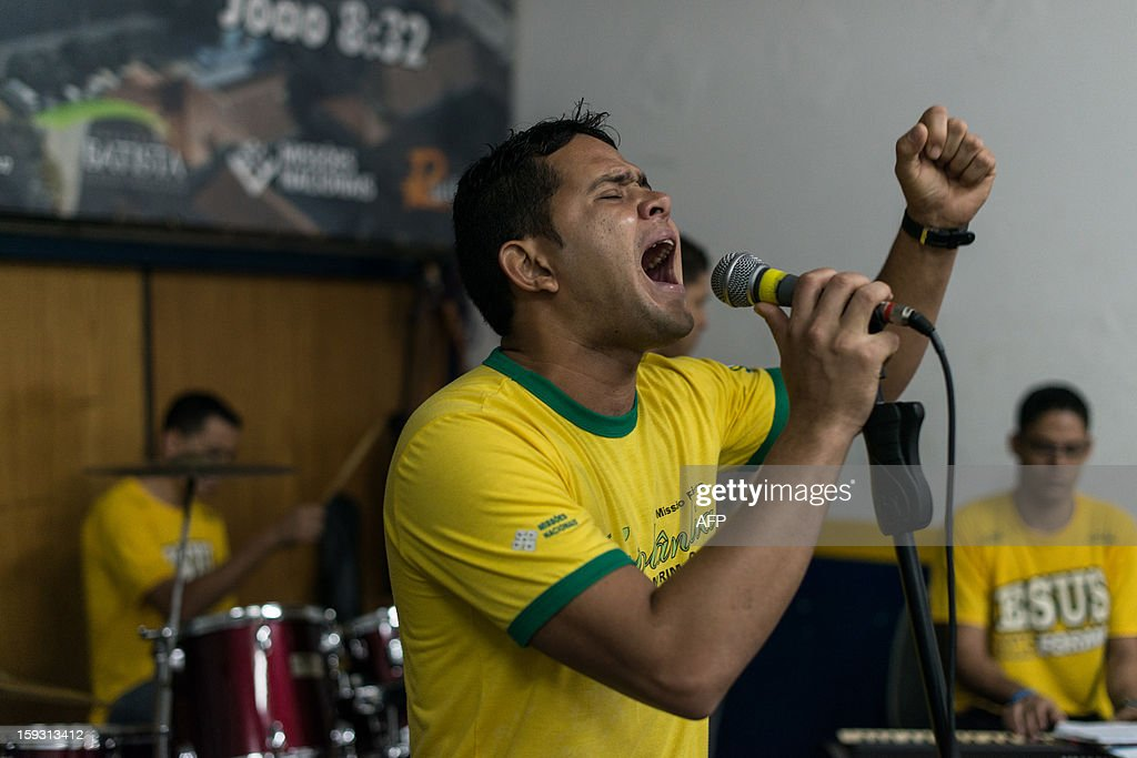 A staff of 'Cristolandia', a Christian church offering free breakfasts, lunches, showers or haircuts, sings during their prayer with crack addicts, in downtown Sao Paulo, Brazil on January 11, 2013. Former drug users or homelesses work as full time staffs at the church. AFP PHOTO/Yasuyoshi CHIBA