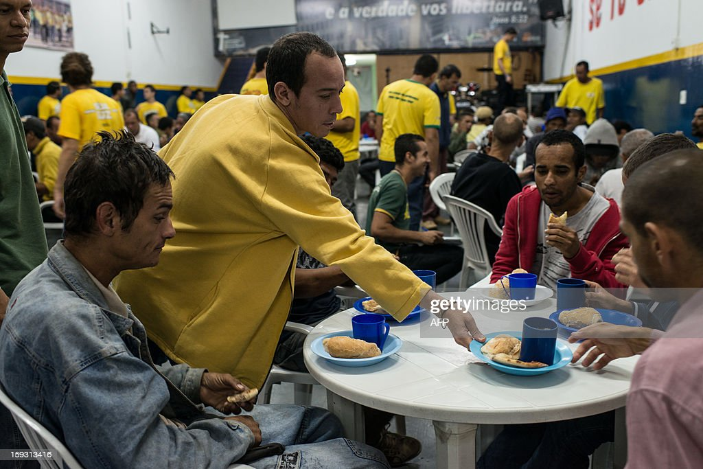 A staff of 'Cristolandia', a Christian church offering free breakfasts, lunches, showers or haircuts, serves food to crack addicts, in downtown Sao Paulo, Brazil on January 11, 2013. Former drug users or homelesses work as full time staffs at the church. AFP PHOTO/Yasuyoshi CHIBA