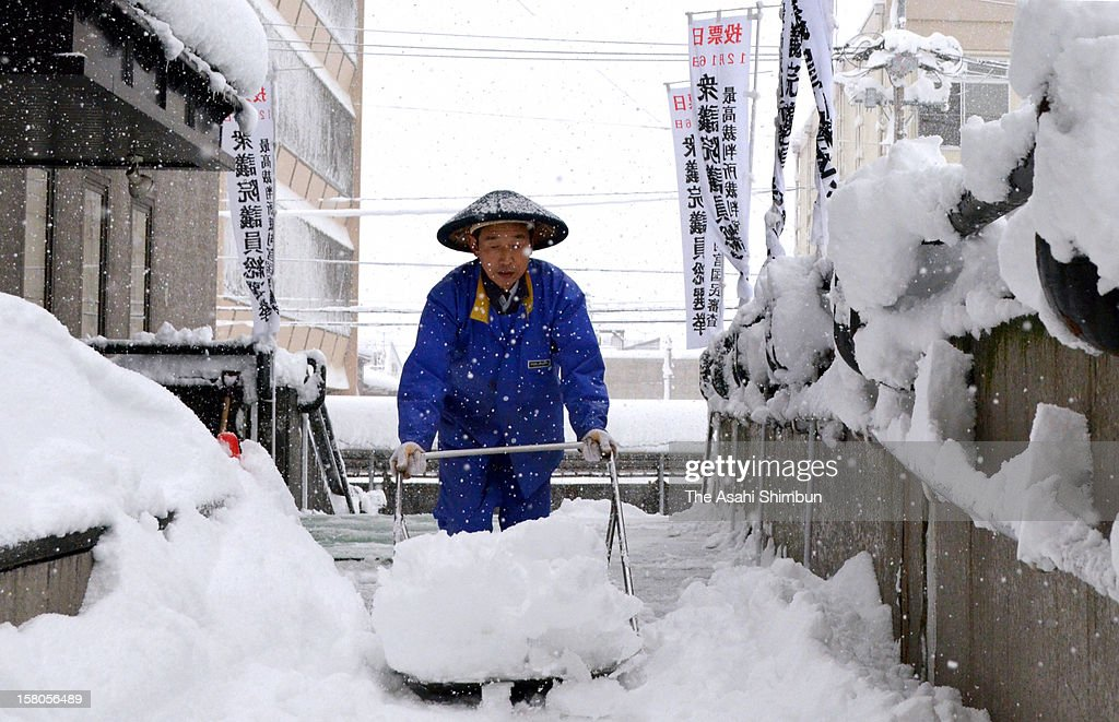 A staff of Tokamachi City Hall removes snow in front of the absentee voting center on December 10, 2012 in Tokamachi, Niigata, Japan. Japan Meteorological Agency issues heavy snow caution to some area due to a low-pressure system stay at coastline of the Japan Sea.