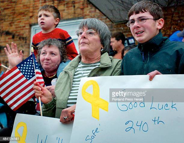 Justin Holbrook right holds a sign while watching his father Lt Col Randy Holbrook depart with the Maine Army National Guard's 240th Engineer Group...