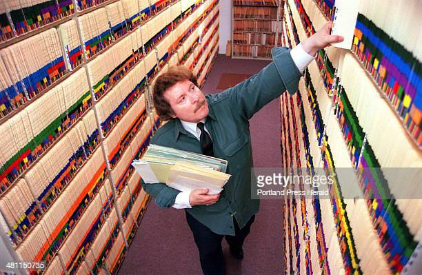 Staff Photo by David MacDonald Mon Jun 18 2001 Herb Adams Cumberland County Probate Court Clerk looks for a will in the courthouse attic storage area