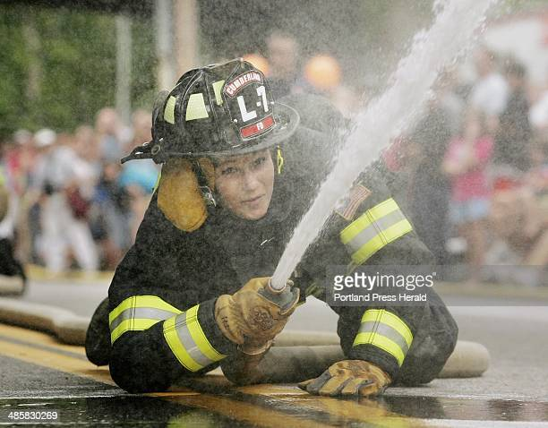 Rachel Storey of the Cumberland Fire Department knocks down the target during the wet hose challenge during the firefighters' muster competition at...