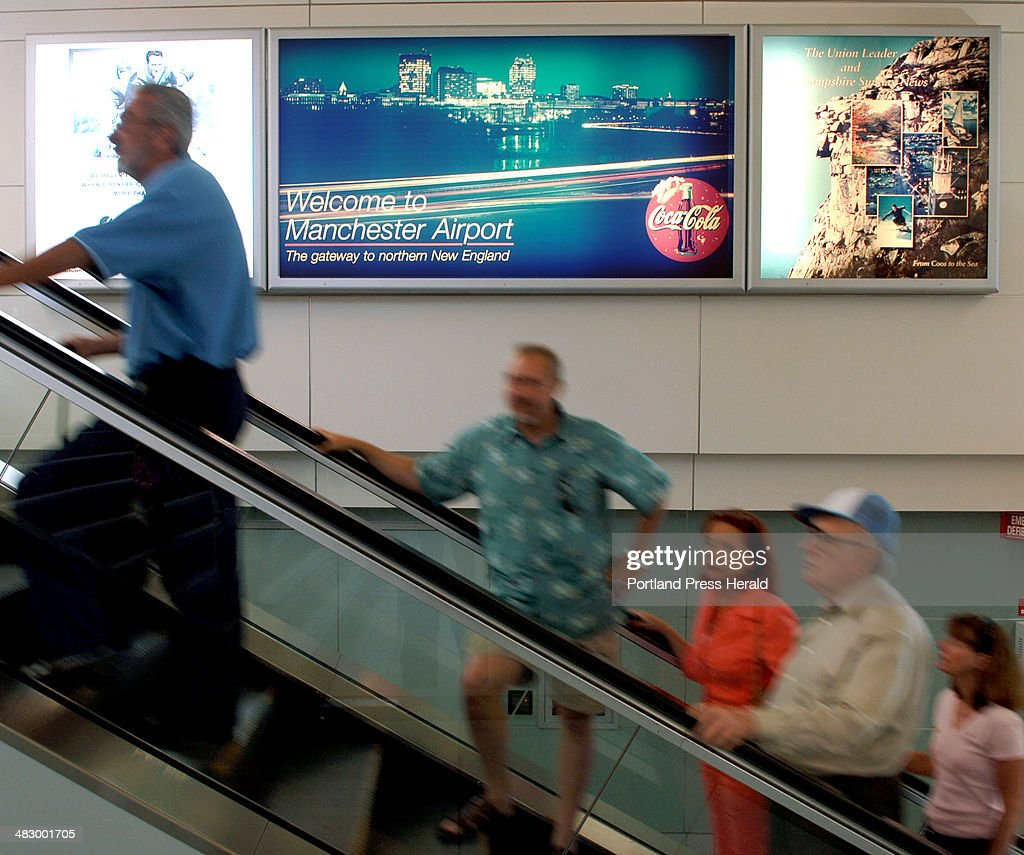 Staff Photo by Fred J Field Saturday july 2 2005 Passengers ride past a sign billing the Manchester NH airport as the gateway to Northwern New...