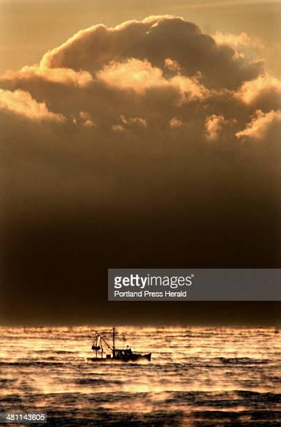 Staff Photo by Fred J Field Sunday February 16 2003With temperature near zero degrees Fahrenheit a shrimp boat heads to sea amid Arctic sea smoke and...
