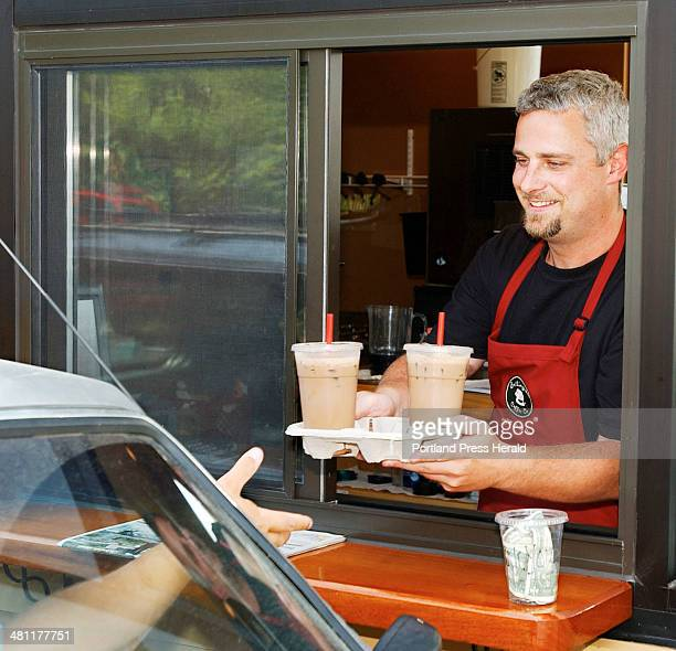 Staff Photo by Gordon Chibroski Tuesday July 8 2003 Craig Rasmusson owner of Bellingham Coffee Co serves a couple of iced coffees through the driveup...