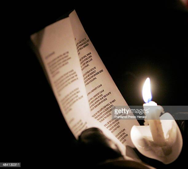 Staff photo by Gregory Rec A candle lights up a caroler's lyric sheet at the Franciscan Monastery in Kennebunk during Christmas Prelude on Saturday...