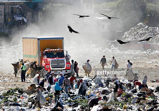 Staff photo by Gregory Rec Guajeros people who scavenge through the dump looking for items to resell run alongside an arriving dump truck in the...