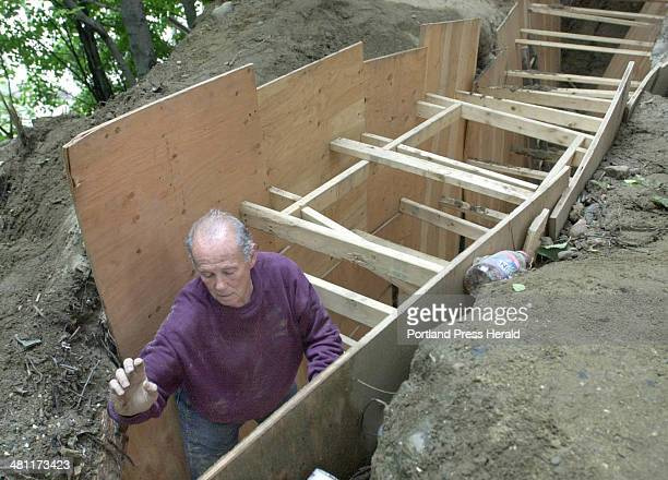 Staff Photo by Gregory Rec Monday July 17 2000 Gordon Simonds climbs out of a trench walled with plywood supported by 2x4 studs behind his property...