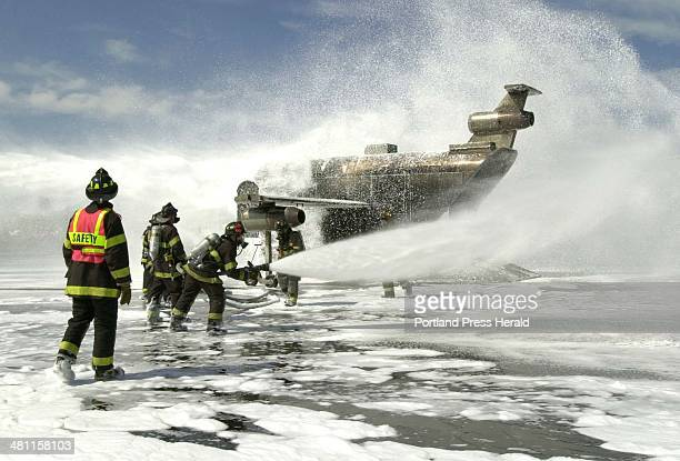 Staff Photo by Herb Swanson Thursday June 7 2001 Firefighters spray foam on a fire training simulator during an aviation emergency exercise at the...